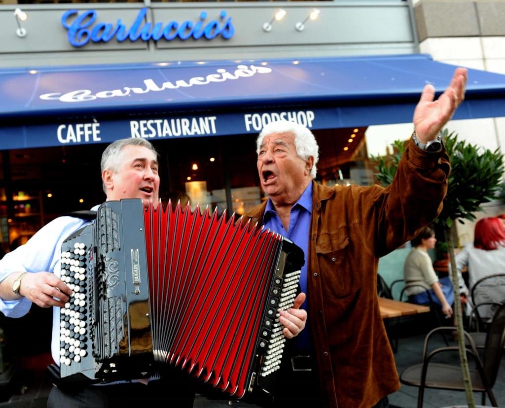 Antonio Carluccio singing with arms in the air with an accordion player outside of a Carluccio's restaurant