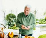 Antonio Carluccio standing at a table in his garden, holding a bulb of garlic, slices of pumpkin on a tray in front of him