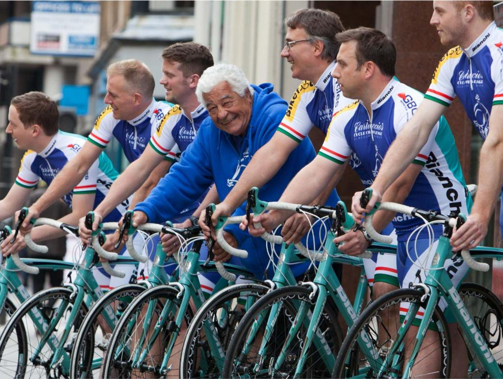 Antonio Carluccio looking at the camera with a happy smile in the middle of 6 other men looking in the other direction, all standing with their racing bicycles